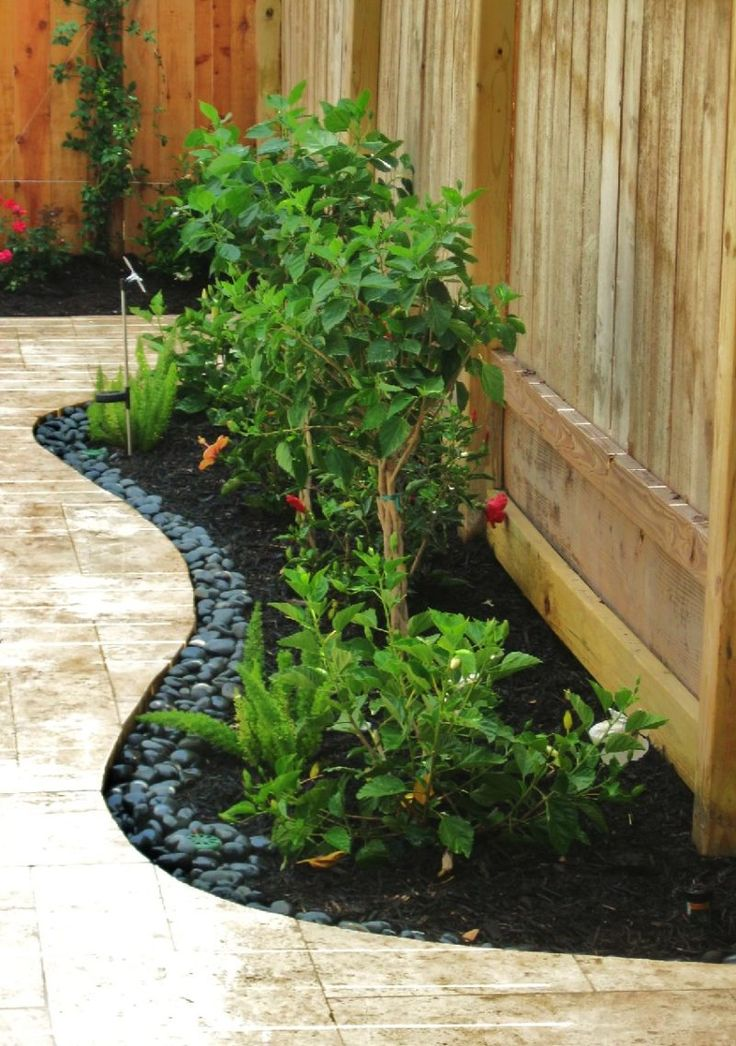 Crushed Black Granite In The Back Yard With Small Garden With Stone Pavers And Plants And Flowers With Wooden Fence