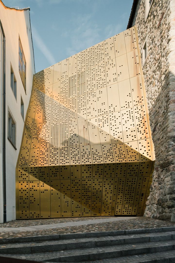 """Name: Janus • Year: 2007 • Architect: MLZD • Location: Rapperswil-Jona, Switzerland • Description: """"In addition to establishing a more intuitive layout, the design seeks to lend a new exterior identity to the museum with a bronze perforated facade that folds between two historic structures."""" — """"Janus"""", iGNANT (Retrieved: 15 May, 2012)"""