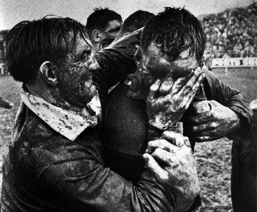 """It appears to be a rugby player force feeding a protester """"mud"""" or a similar substance, this is the typical activity you would see at a game where protesters and angry rugby fans were present"""