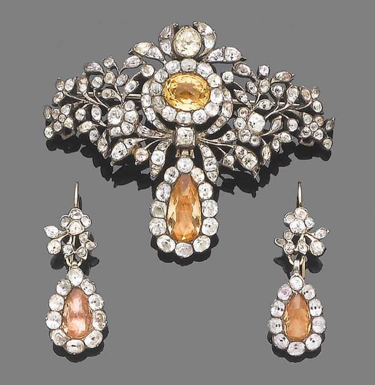 An 18th century topaz and paste brooch and a pair of earring  The openwork lozenge-shaped plaque, circa 1770, of floral and foliate motifs, set throughout with mixed-cut pastes, centrally-set with a faceted yellow topaz in a foiled closed-back setting, suspending a similarly-set pear-shaped topaz drop, accompanied by an associated pair of earrings, earrings later converted, lengths: brooch 7.2cm., earrings 4.4cm.