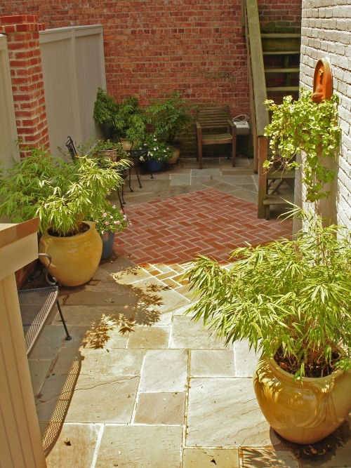 """multiple materials - """"area rug"""" of brick set within flagstone patio"""