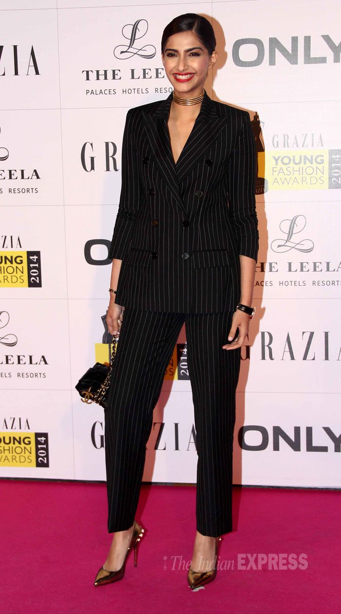 Grazia Young Fashion Awards (April) 2014, Sonam in pinstripe double-breasted suit, with vintage Givenchy necklace, hair in a knot, McQueen pumps