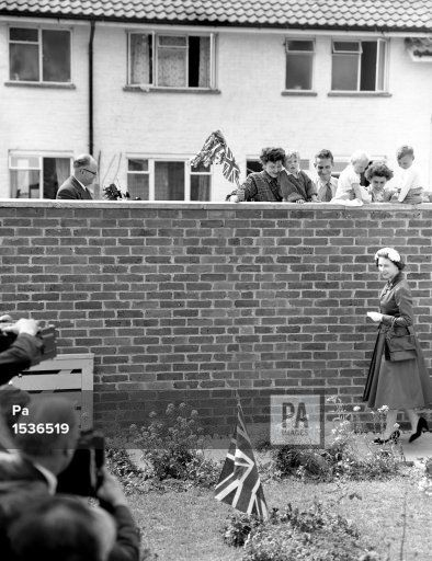 A Union Jack planted in the garden caught the Queen's attention, but she is the object of the neighbours' gaze. They watched as she arrived to visit the home of Mr and Mrs Eddie Hammond at Crawley New Town, Sussex after opening Gatwick airport.