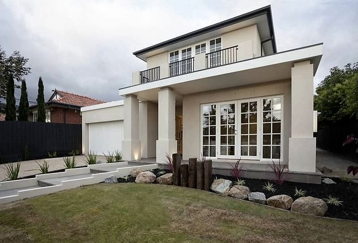 French doors with their multiple panes team with bold columns to present an air of uncluttered grace and dignity. www.davidreidhomes.com.au