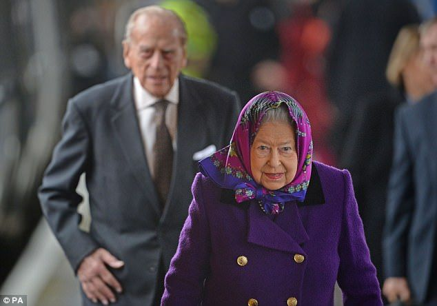 Colourful: The Queen finished her festive look with a vibrant silk headscarf, black Launer...
