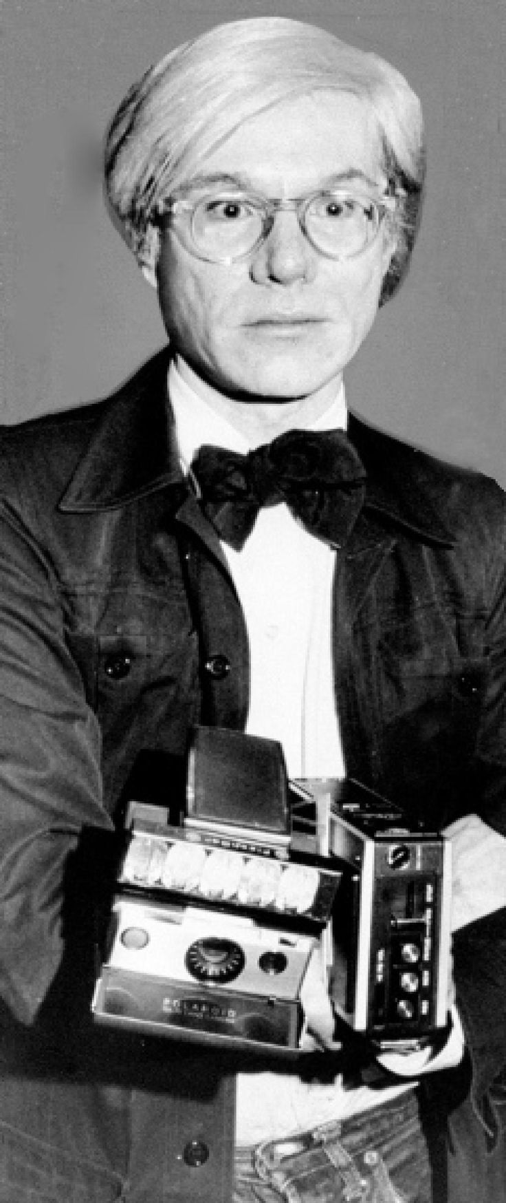 1973: Andy Warhol with tools of his trade: a Polaroid camera and tape recorder.