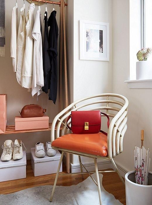 A Glamorous (and Renter-Friendly) Bedroom Makeover Idea -- Love this vintage peach and white midcentury chair with a red structured cross body bag on top in the corner of this bedroom, designed for Instagram star Grace Ban, decorated by our Weekend Decorator, Megan Pflug! See the before and after, and get the scoop on how to DIY your own gorgeous gold faux-canopy bed and create a glamorous feminine bedroom style on our Style Guide!