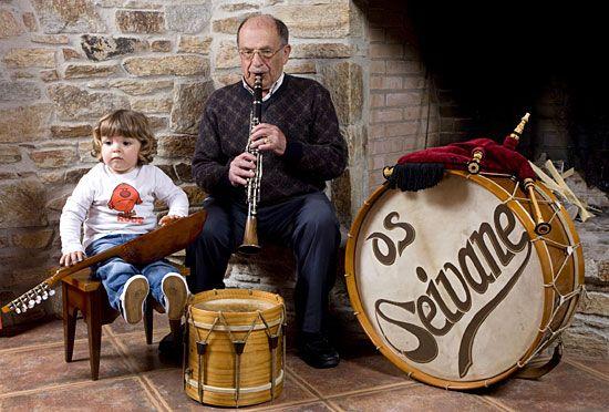 """Brais escoita atento ó seu bisavó mentras intenta arrancar unhas notas ó """"charango"""", 2010."""