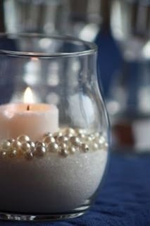 Sand (or sugar), faux pearls, candle  Simple decor idea I like if it fits in the budget/vendor doesn't already include decor. Could be cheap to make (Dollar store items).