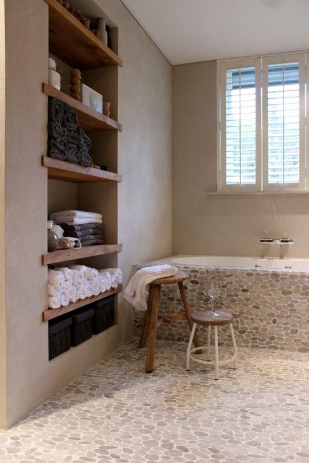 Wat een leuke badkamer met die kiezels, leem stucwerk, inbouwkast en shutters!