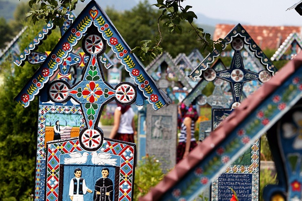 """""""Fröhlicher Friedhof"""" im Ort Săpânţa    The Merry Cemetery (Romanian: Cimitirul Vesel) is a cemetery in the village of Sãpânta, Maramures county, Romania,that is famous for its colourful tombstones with the native paintings that represent scenes from the life of the buried persons and even poetry in which those persons are described."""
