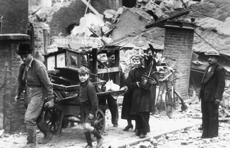 This photo was taken on 16 October 1940. It shows a family with their belongings on a hand cart after their London home was bombed.