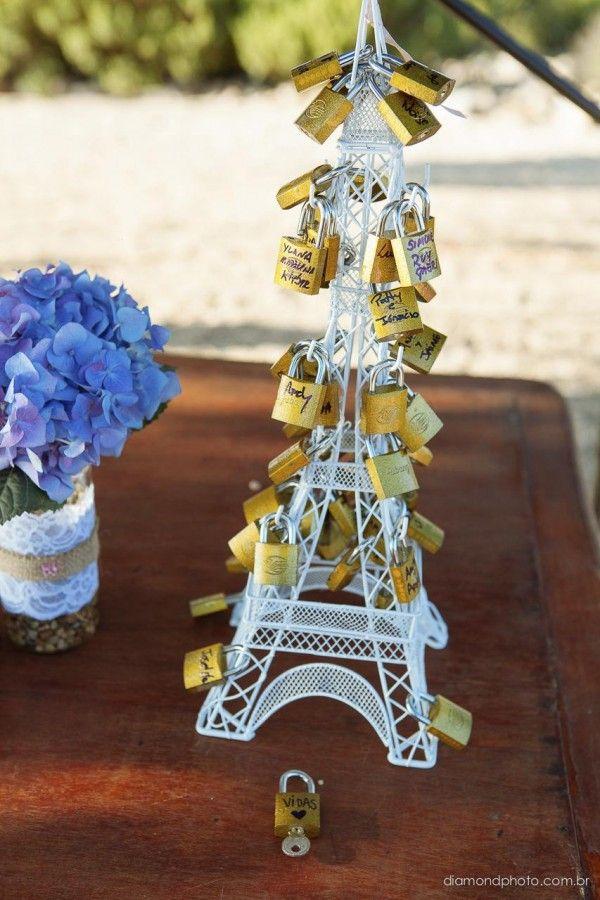 """Na cerimônia teve uma mini Torre Eiffel para os convidados escreverem seus nomes nos cadeados. Ficou completo quando os noivos escreveram seus nomes no último cadeado e colocaram na Torre, após os votos. """"Nesse momento o celebrante relembrou um pouco o ritual da Ponte do Amor (...)"""