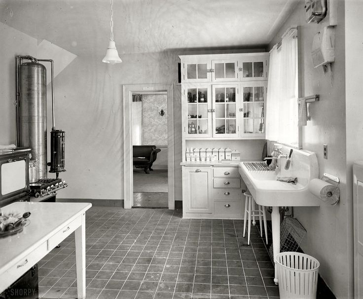 From Shorpy: Restoration Hardware, 1920. Look, another dish rack stashed under the sink and paper towels hung on the wall. That garbage can is really interesting too. Those canisters on the back cabinet are fantastic. I'd love to find some of those.