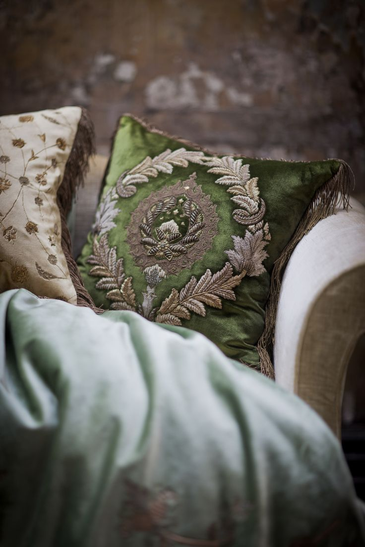 Opulently embroidered raised laurel wreaths surround a finely worked central motif in subtly aged gold and silver thread