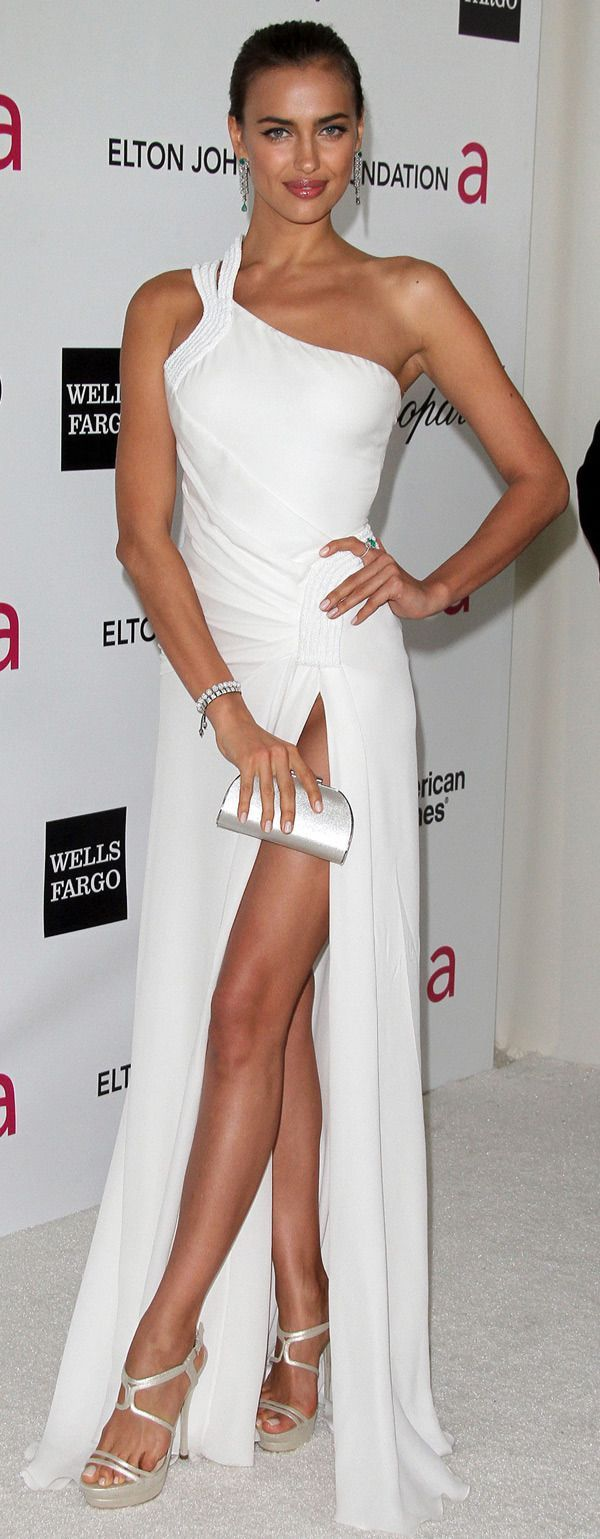 Opt for a white evening dress and you'll look stunning anywhere anytime. A pair of silver leather heeled sandals will be a stylish addition to your outfit.  Shop this look for $96:  http://lookastic.com/women/looks/heeled-sandals-evening-dress-bracelet-clutch-ring-earrings/6637  — Silver Leather Heeled Sandals  — White Evening Dress  — Silver Statement Bracelet  — Silver Leather Clutch  — Green Statement Ring  — Green Statement Earrings