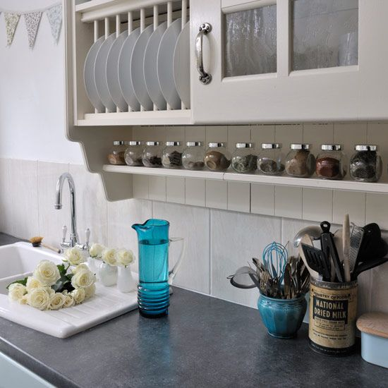 Small kitchen with white splashback tiles, grey laminate worktop and cream storage cupboards and spice rack