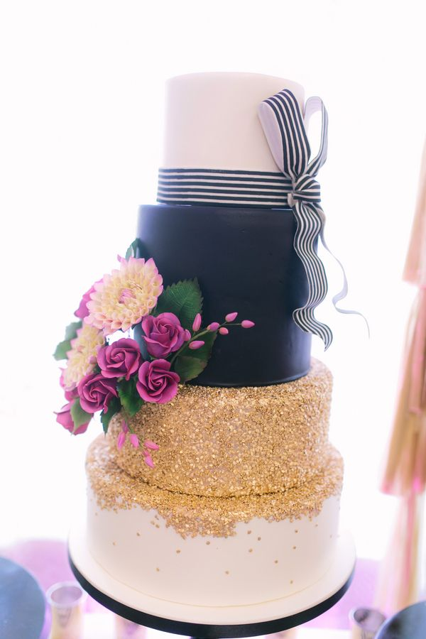 fabulous wedding cake, featuring a black and white striped fondant bow, edible gold glitter, and purple flowers. By LoveBirds Sweets