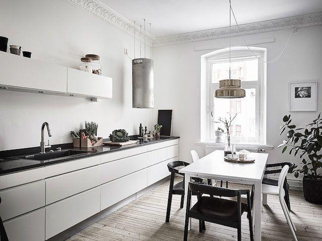 Sleek white kitchen with wood floors in a calm swedish home in grey and white. Entrance.