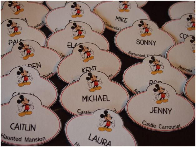"As a combination favor/placecard, we made mock Disney cast member name tags by printing a design on cardstock and gluing it to a plastic nametag purchased in bulk off the internet. The bottom of the nametag gave the ""ride"" at which table the guest was seated. Almost everyone got in the spirit by putting on their nametags!"