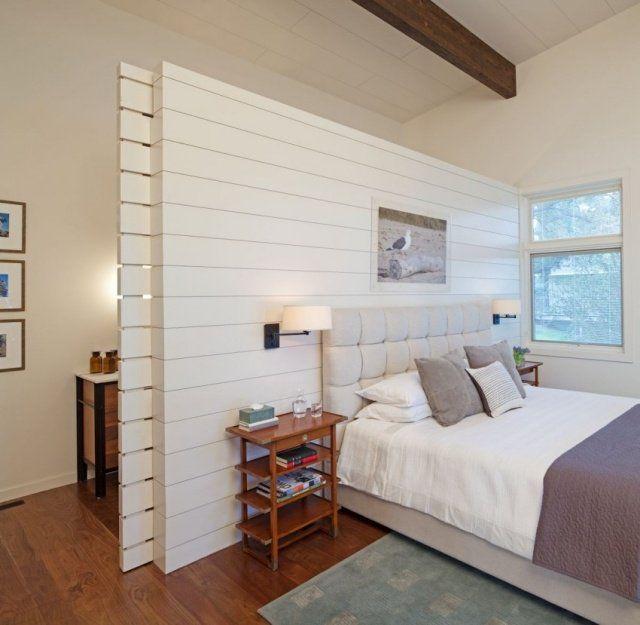 Dans cette chambre, on a créé une cloison en tête de lit : ceci permet d'établir une séparation contre laquelle appuyer le lit, et de dégager un espace séparé pour une petite salle de bain. La cloison n'atteint pas le haut du mur, afin de ne pas casser les lignes de perspectives et d'éviter un cloisonnement excessif.