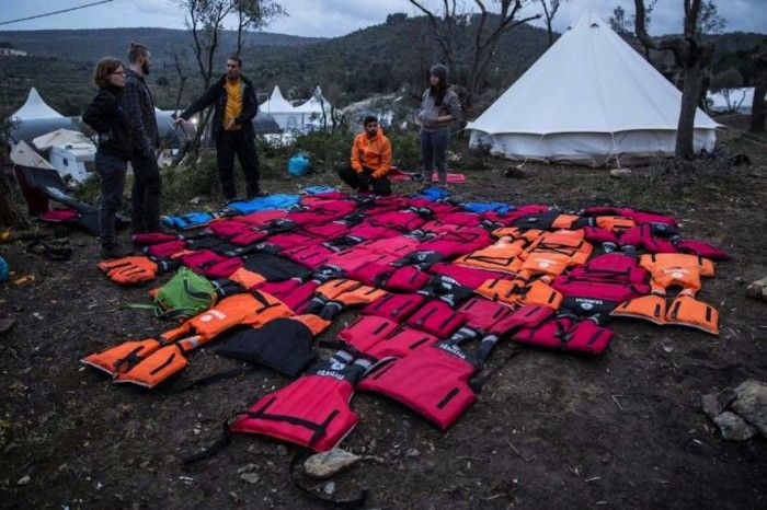 Mads Damgaard Peterson (centre) stands in front of a large mattress made from repurposed life-jackets at Moria refugee registration centre on Lesbos.