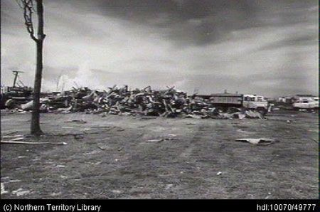 Clearing up after Cyclone Tracy. Sheet iron roofing stacked, waiting for removal to trucks. Northern Territory Library.