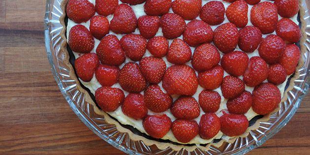 Jeg kan slet ikke stå for den her jordbærtærte med en sprød mørdejsbund, lækker vaniljecreme med hvid chokolade og masser af søde danske jordbær på toppen.