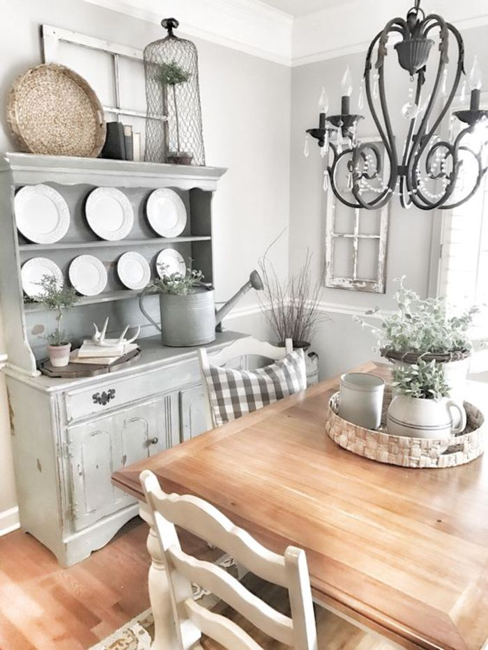 round white plates, on pastel grey dresser, vintage chic style, black wrought-iron chandelier, square wooden table with chairs