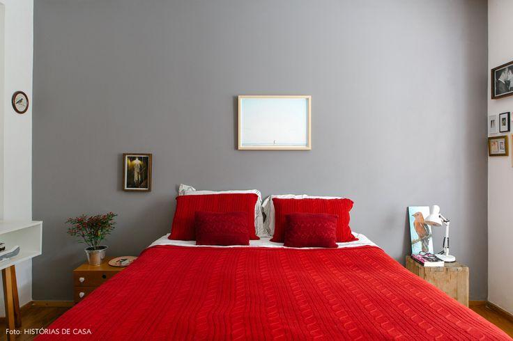 Quarto de casal tem parede ointade de cinza e roupa de cama de tricô na cor vermelha.