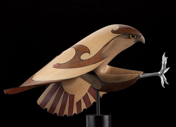 """Medium: kauri, paint, ink, aluminum talons, metal connections, base painted aluminum / MDF. Size: 19 x 15 x 15 inches (incl. base). """"Raptors, from curious little owls to large powerful eagles, are probably my favourite subjects. Hawks and falcons with their streamlined shape and ferocious demeanour always appeal."""