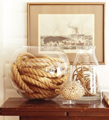A large round glass vase seems like the perfect vessel to hold and display a coiled heavy rope. Via House and Home.