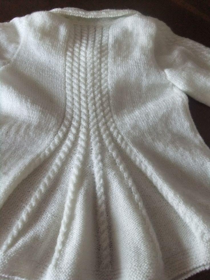 Detalle de la espalda de la chaqueta trenzada blanca y larga para niña. Hecha por María Landín