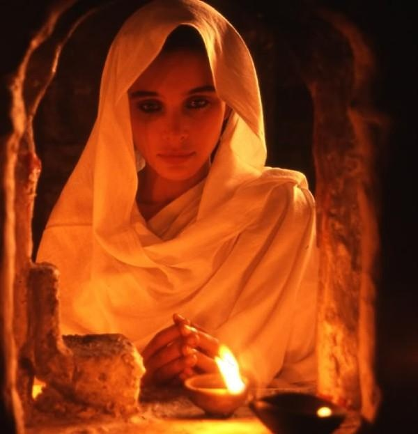 Jewish Woman saying Shabbat prayers for the family before eating.