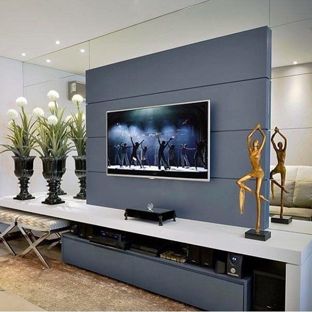 Para ampliar e proporcionar leveza para este Estar a parede atrás do painel  da TV foi revestido com faixas de espelho prata. Destaque para o painel em MDF azul. Projeto: Vobol Arquitetura.