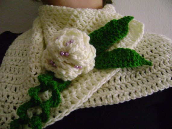 Beige button scarf with flower and green leaves.