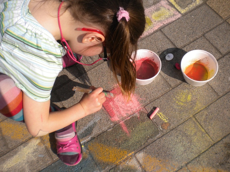 Krijt raspen over potje met water, er buiten mee schilderen op de grond