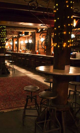 The Tippler Bar is hidden below Chelsea Market, NYC, and is a super-cozy, subterranean winner. Its exposed brick, reclaimed water tower wood, and old train rails from the Highline give the place a hip vibe. The bar is always bustling, fortunately it's a pretty relaxed crowd.