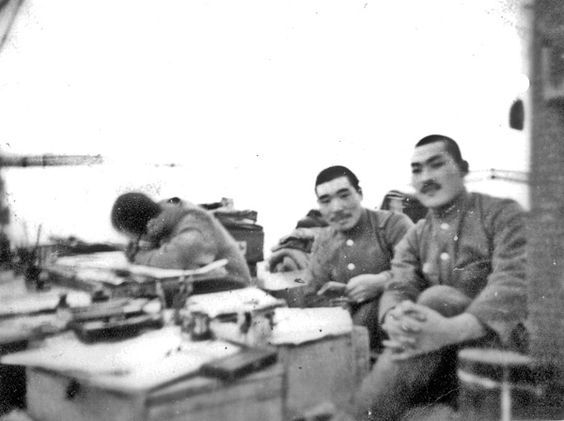 """THE JAPANESE ON ATTU  """"Apparently this photo was taken in an office environment. The illumination from the background was the sun shining on that side of the tent. These individuals appear to be middle-level management officers."""" (11–30 May 1943, more than two week battle ended when most of the Japanese defenders were killed in brutal hand-to-hand combat after a final banzai charge broke through American lines.)"""