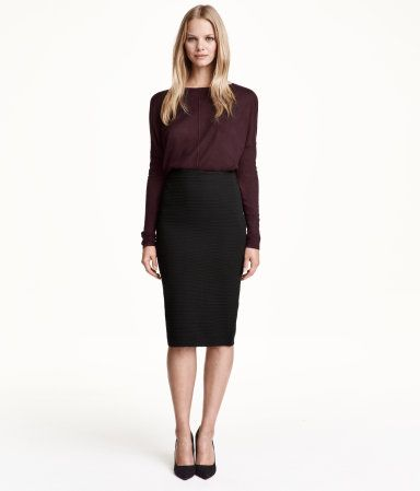 Pencil skirt in thick jersey with an elasticized waistband, concealed back zip, and slit at back. Unlined.