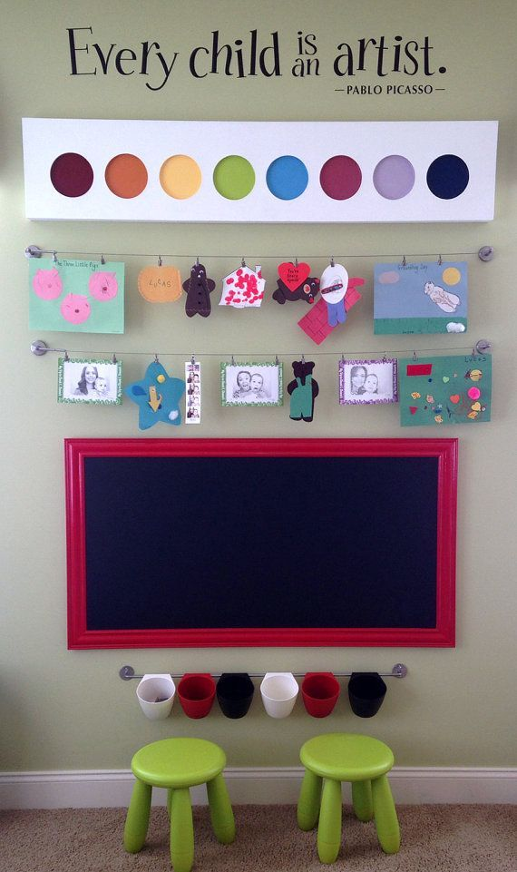 I love this idea of having an art area in a kids' playroom, especially having an area above the blackboard to showcase the finished artwork.