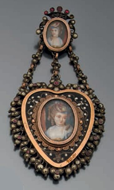 A 19th century heart-shaped reliquary pendant, containing two painted female miniatures, decorated with enamel and garnets, mounted in 18k gold and silver.