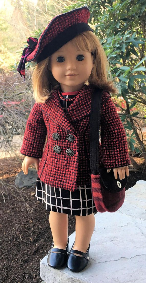 6 Piece red and black outfit created for your 18 doll, such as American Girl®, features a jacket with pleats in the back over a black and white shift dress with contrasting red belt. Matching beret and handbag and a beaded crocheted necklace complete the look. The jacket features black piping around collar, seams, sleeves and back pleats with a Hong Kong binding on the inside facing. The jacket closes with velcro dots under nickel buttons. The matching beret has black piping and a jersy…