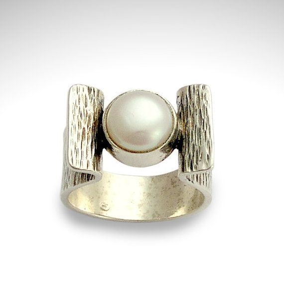 At first light ~~~~~~~~~~~~~~ A very artistic extraordinary design . a beautiful fresh water pearl is inlaid in a smooth sterling silver bezel soldered to the sides of the open grooved ring.(CODE-R1531S) © 2011 Artisanimpact Inc. All rights reserved. Construction & Dimensions: