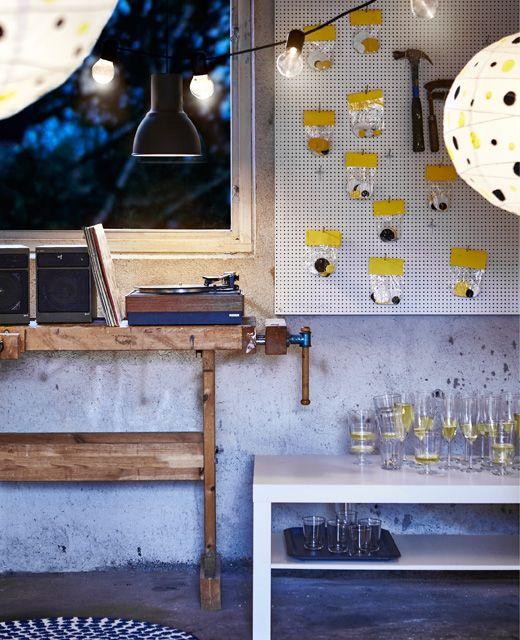 Eine Werkzeugstecktafel mit Konfettitüten daran neben einer Werkbank, auf der die Musikanlage steht. Darüber hängt HEKTAR Hängeleuchte in Dunkelgrau.