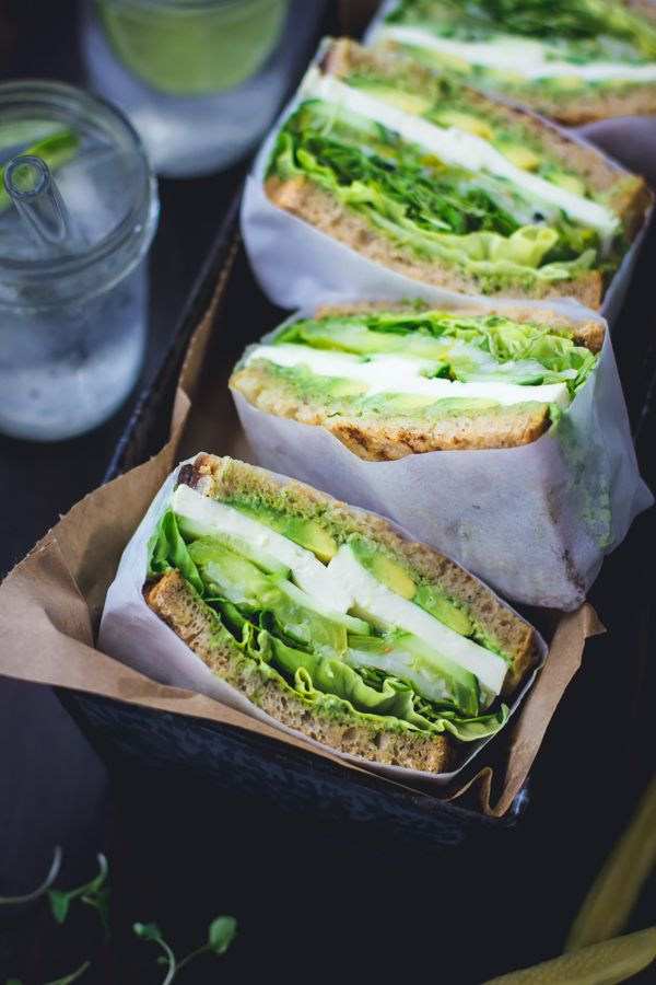 Green Goddess Sandwiches with avocado, fat slices fresh mozzarella, heirloom tomatoes, cucumber, butter lettuce, and pickled spring onions