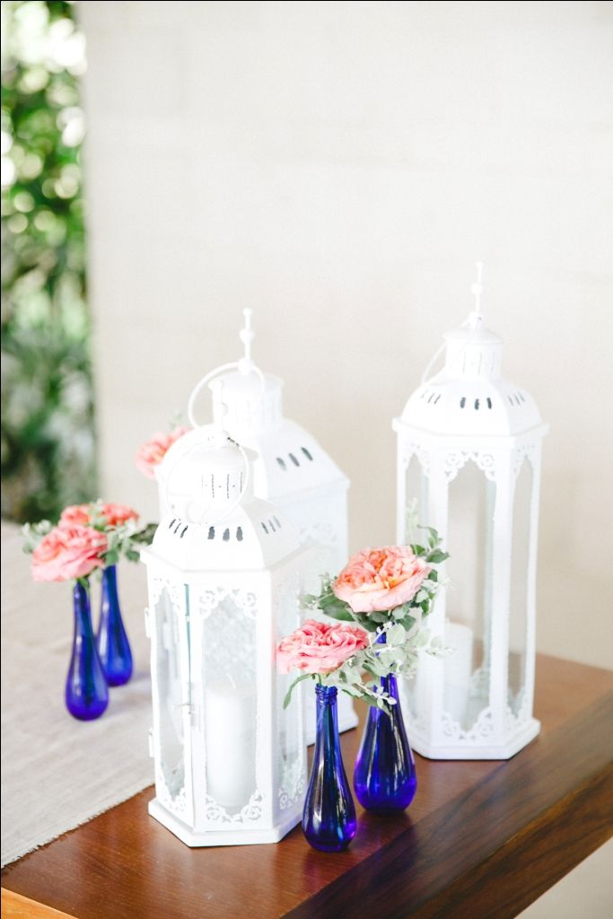 Registration table adorned with lanterns and flowers in blue jar