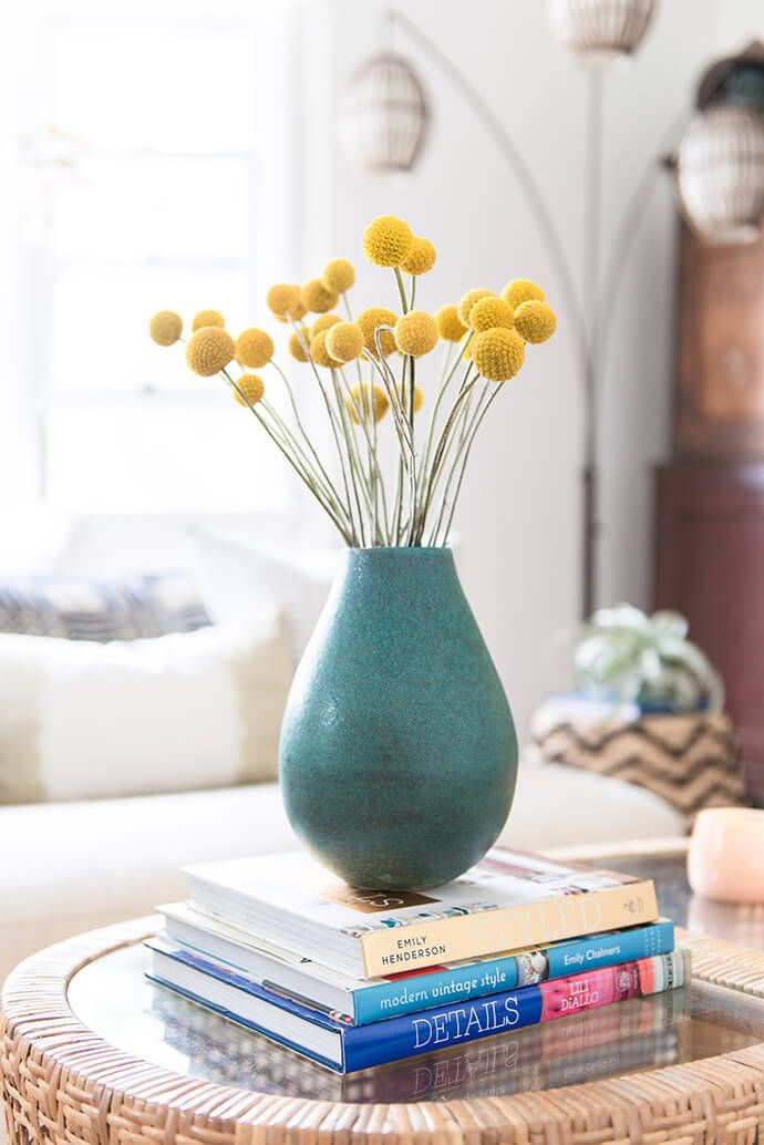 yellow billy button flowers in teal vase