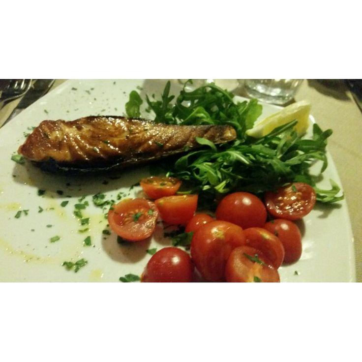 Trancio di salmone agli agrumi scottato in padella con rucola e pomodorini