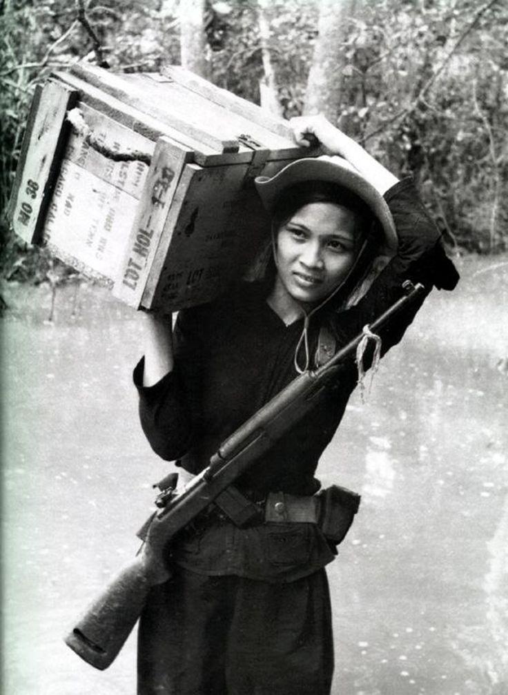 Female member of Vietnamese Popular Forces (South Vietnamese village defense) unit carries ammunition box. circa 1967.